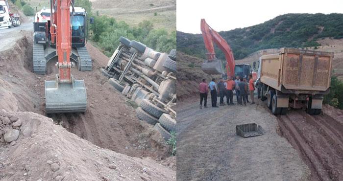 Yolun kenarına devrilen iş makinesi kurtarıldı